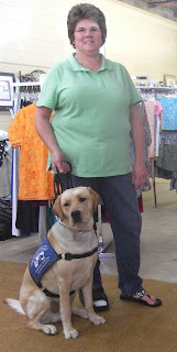 Picture of Toby wearing his coat in a sit-stay beside the consignment store owner (who is wearing jeans & a green shirt)