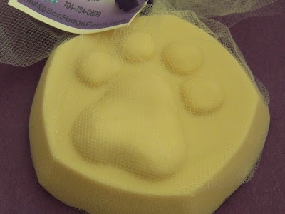 Picture of a bar of goat milk soap - which has a puppy paw shape on the top