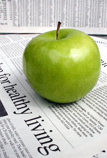 newspaper article and green apple