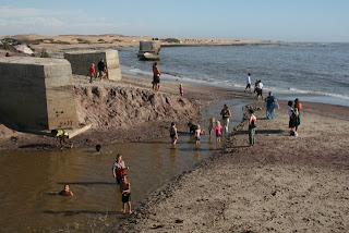 People play in the Swakop River as it flows into the Atlantic