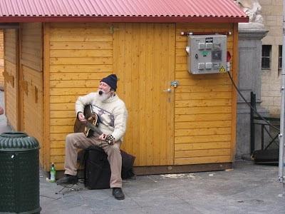 un vieil homme barbu chante devant une cabane en bois