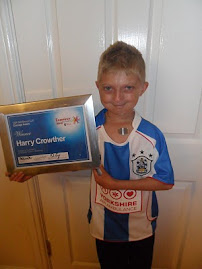 Harry with his Examiner Community Courage Award and T-shirt from Huddersfield Town Football Club