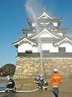 天守閣の周囲に放水する消防署員