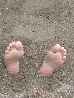 feet sticking out of the sand
