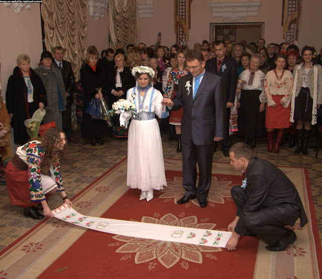 Unfolding a ceremonial towel at wedding in Ukraine