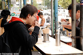 Men eating ramen noodle on the street near a market