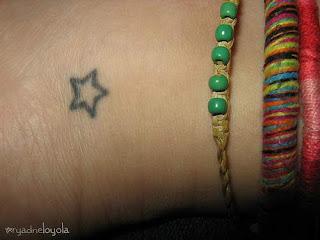 Pequena e solitária estrela simples sem preenchimento de cor tatuada no pulso
