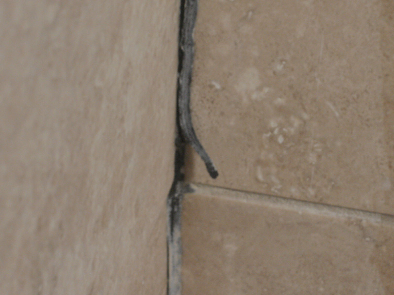 in this shot you can see where the caulk has failed and mold is permeating into the corner when water continues to seep into the seam between the tile and