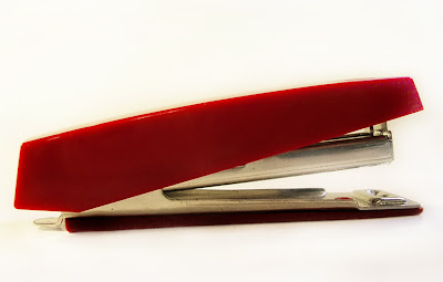 a small modern stapler in bright red, copyright J. Gracey Stinson