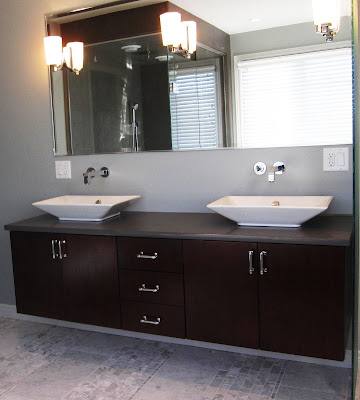 Trend A floating dark maple cabinet with gray quartz countertop Kohler us Reve vessel sinks and wall mounted sleek chrome faucets keep the look modern with u