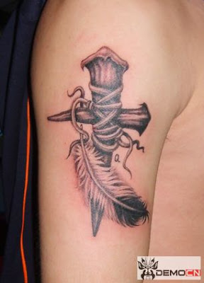 A cross tattoo on the arm with a feather close by.
