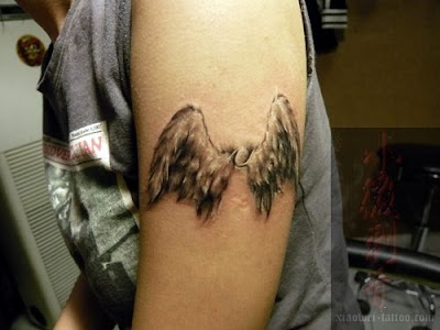 Two angel wings tattoo on the arm.