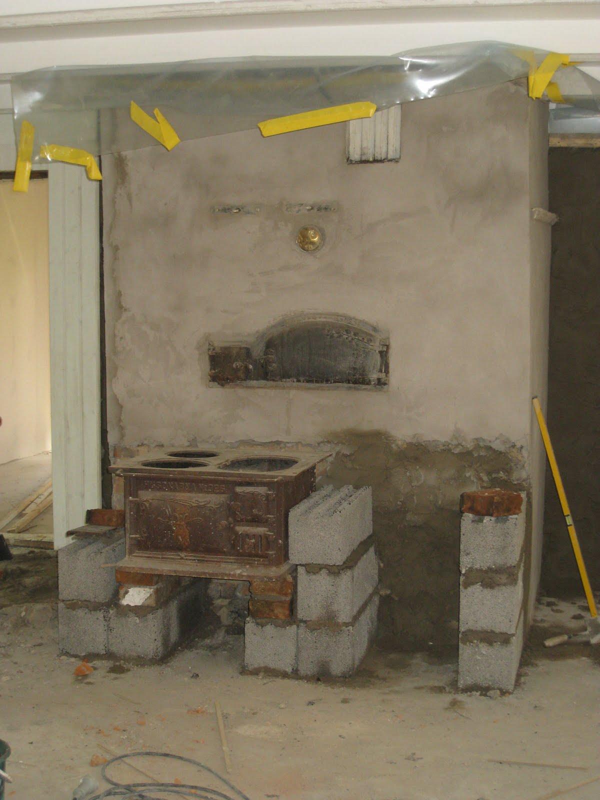 Vedspis Koket : Pappa Per har putsat murstocken och nu murar han upp for vedspisen