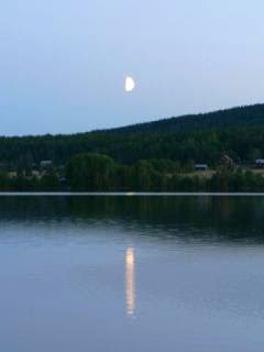 photograph of moon and its shadow falling on the lake.