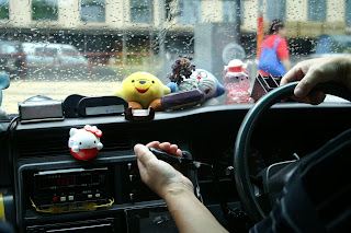 Image of the dashboard and driver's hands of a taxi I was in the other day. Upon the dashboard are a raft of stuffed animals