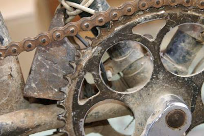 image of a Chinese bike, close focus on the major chain wheel, with a small weight affixed to the shaft by a wire.