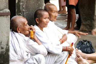 Image of Buddhist nuns sitting in the courtyard of Angkor Wat