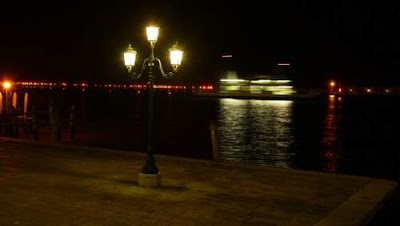 Image of a ferry and lit piles in Venice's lagoon.
