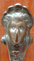 Image of a Venetian doorhandle, with a worn off nose and  mouth, and sad eyes.