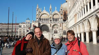 Image of the Basilica of St. Mark behind four handsome people