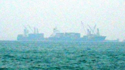 Image of international shipping vessels in the Territorial waters of Hong Kong, just arrived from the High Seas. These ships are shrouded by mist and by distance, but they are visible to the law and those laws regulate their activities and protect us all, from owners to workers and from fishers to fish to consumers of fish.