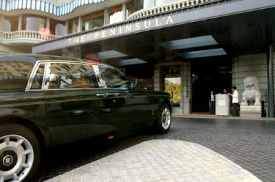 Image of the Peninsula Hotel, Kowloon, Hong Kong, and one of the hotel's fleet of Rolls Royces which are available for the guests.