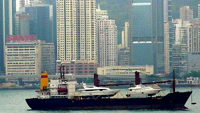 Image of two luxury yachts being transported into Victoria Harbour, Hong Kong, on top of a freighter.