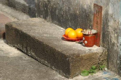 Image of a small, sidewalk shrine (in Hong Kong's New Territories) for local residents to provide offerings to one member of the pantheon of Chinese gods and goddesses to elicit better luck or outcomes or treatment...