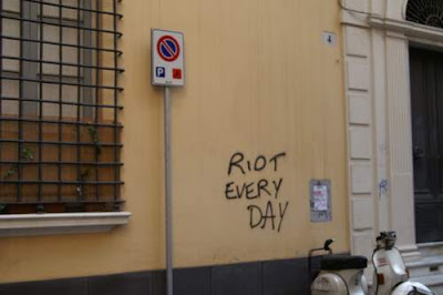 Graffiti image of the phrase 'riot every day' found on a peaceful street, above a parked Vespa which is parked in a no-parking zone, from the old town centre of Genoa, Italy.