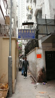 Image of the narrow start of the alley in Kowloon, Hong Kong, looking backwards after walking in it for 30 metres.