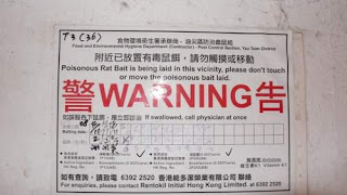 Image of a sign in a Kowloon, Hong Kong, alley warning people not to touch the poisoned food. It's for the rats. Hopefully they cannot read. The rats, that is.