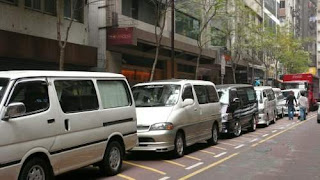 Image of a row of grey-market transport vehicles, in Hong Kong, waiting for grey-market goods to be loaded for shipments to the port.