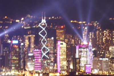 A blurred image of Hong Kong Island's skyline, lit up at night.