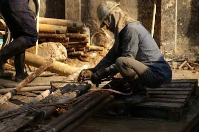 Image of a Hong Kong construction worker cutting through pipes with an oxy-acetylene burner wearing rubber boots, now out of the mud, crouched on top of wooden pallet.