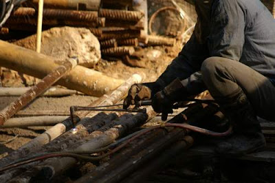 Close-up image of a Hong Kong construction worker cutting through pipes with an oxy-acetylene burner wearing rubber boots, now out of the mud, crouched on top of wooden pallet.