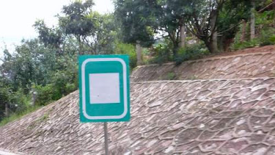 Image of a roadside sign, in China, with a massive white square inside another white square, superimposed upon a green background.