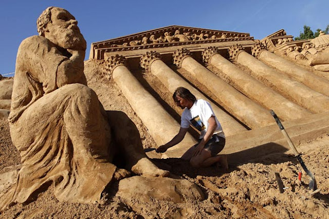 sculptor works on a sand sculpture of The Thinker