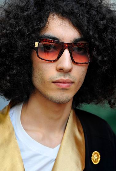 This is a fashion guy who wear cool curly African American hairstyle.