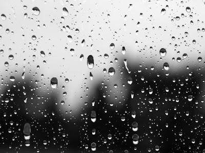 Gotas de chuva perdidas na escuridão da noite, escorrem pela sufocante janela da minha sala
