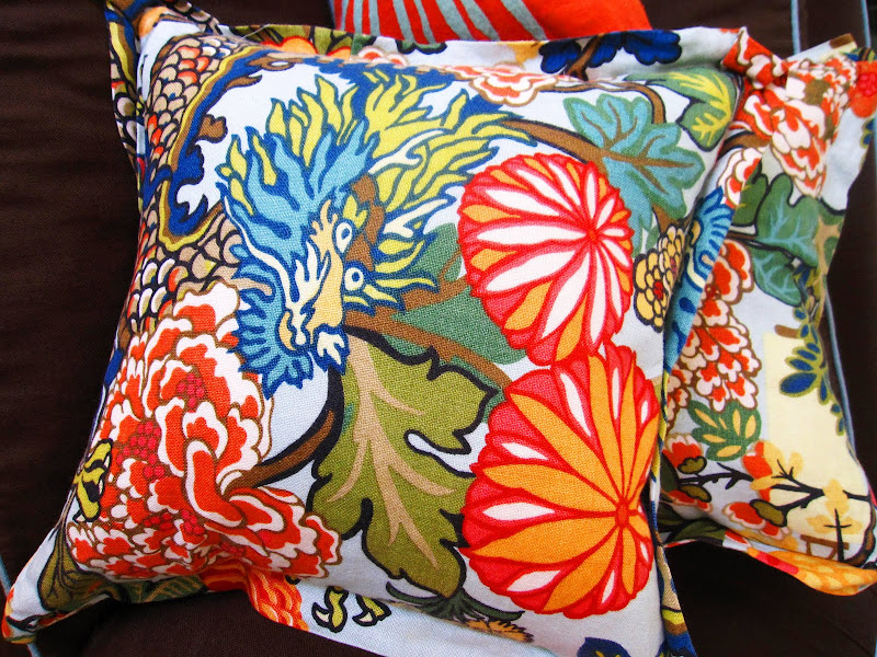 Two Schumacher's Chiang Mai Dragon pillows on a brown sofa with blue piping