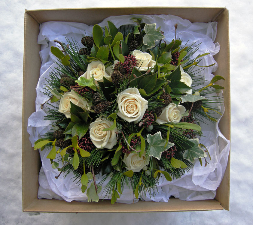 Winter wedding bouquet with a strong Christmas look of roses holly ivy