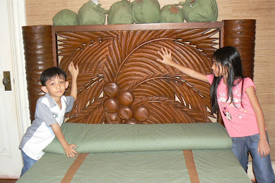 Carved wooden headboard of a bed in the Coconut Room