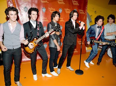 The Jonas Brothers pose with wax replicas at Madame Tussauds Wax Museum in Washington, D.C. - Photo courtesy of Getty Images/Paul Morigi and E!Online