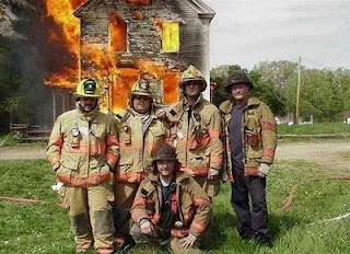 funny photo of firemen posing for picture while house is on fire behind them