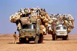 funny desert photo of overloaded trucks with goods and people