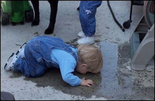funny kids drinking water from puddle or pavement very odd photo