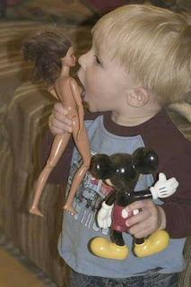 funny photo of young boy playing with doll licking breast