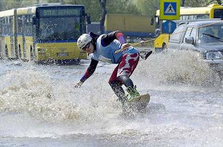 funny crazy photo of man water skiing in flood on road