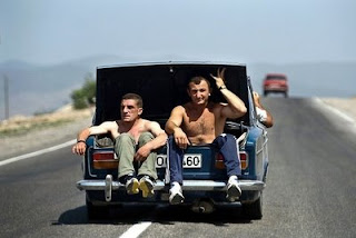 funny car photos two men riding in trunk of car on highway
