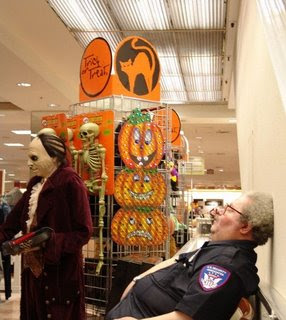funny photo of security guard asleep on the job at halloween store